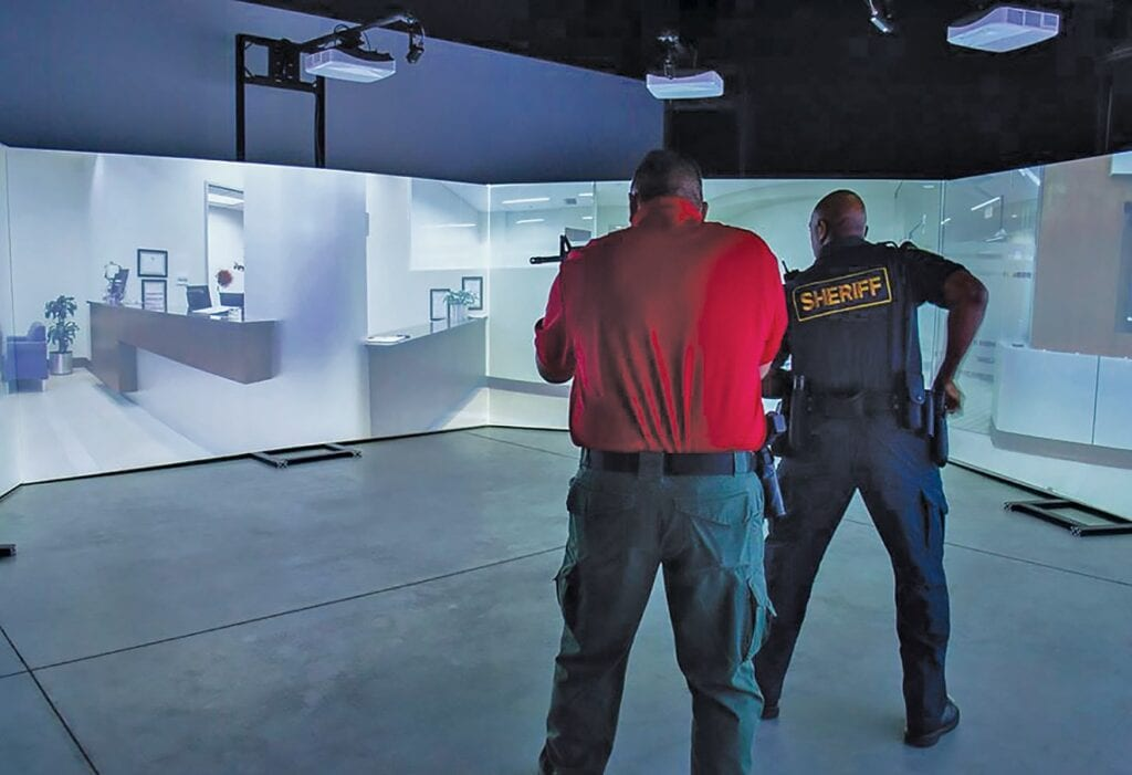 Officers demonstrate the use of force simulation program. -photo credit | Facebook