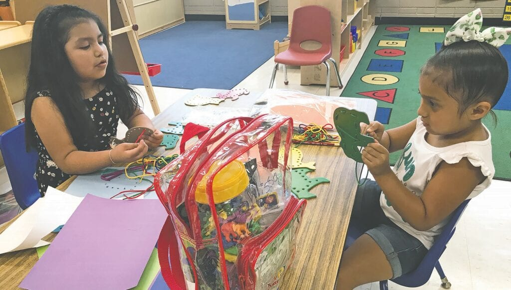 Preschoolers Ximena and Jahlissa use sewing cards to develop fine motor and visual perceptual skills at Ratchford Child Development Center.