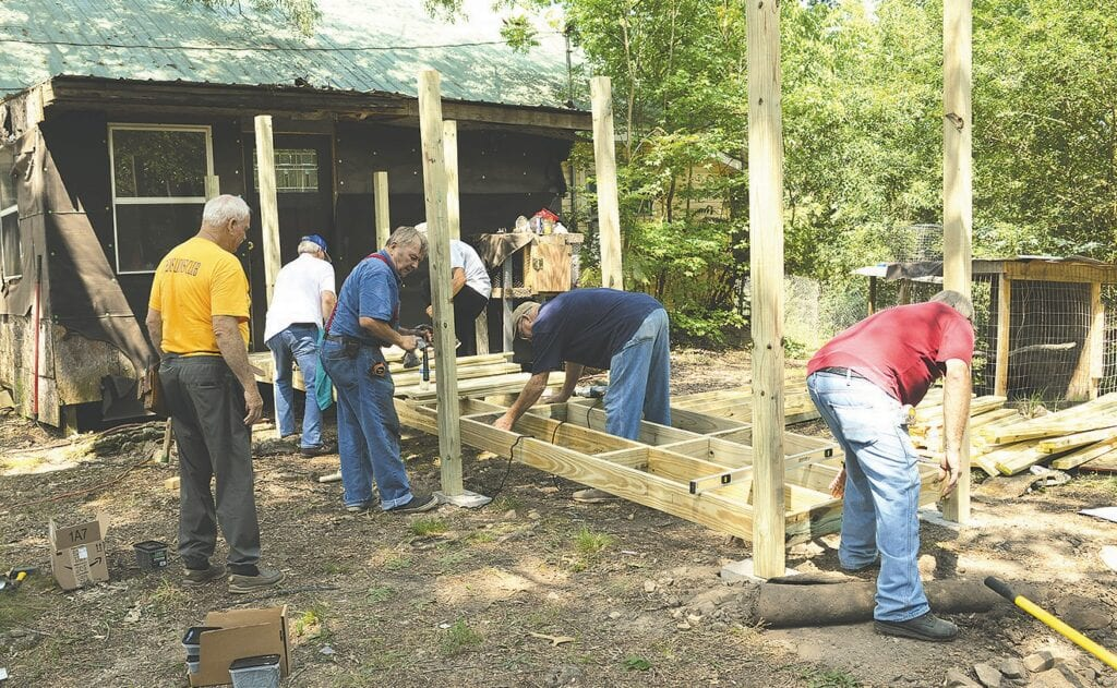 Volunteers from several organizations build a wheelchair ramp at the home of Mylan Self.