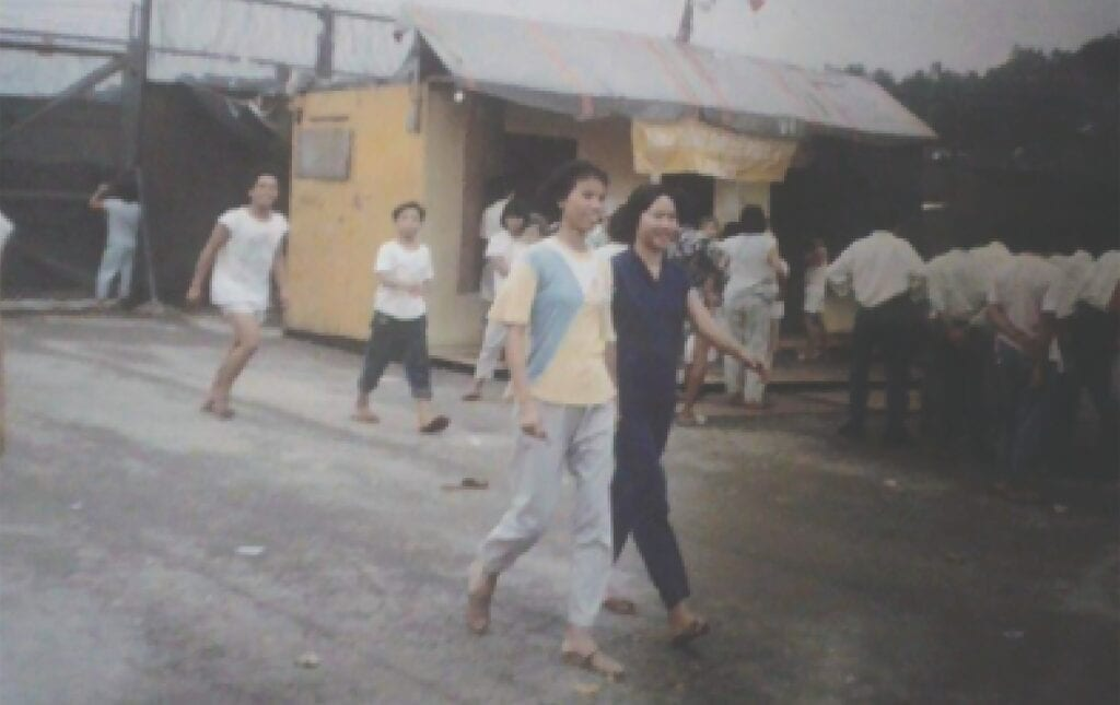 Thuha Le (yellow shirt) and friend stroll through Seekong Camp in Hong Kong in 1991. Behind the girls is a Buddhist temple built by refugees from scrap lumber. Inset: Le and son Nam. -photos courtesy of Thuha Le