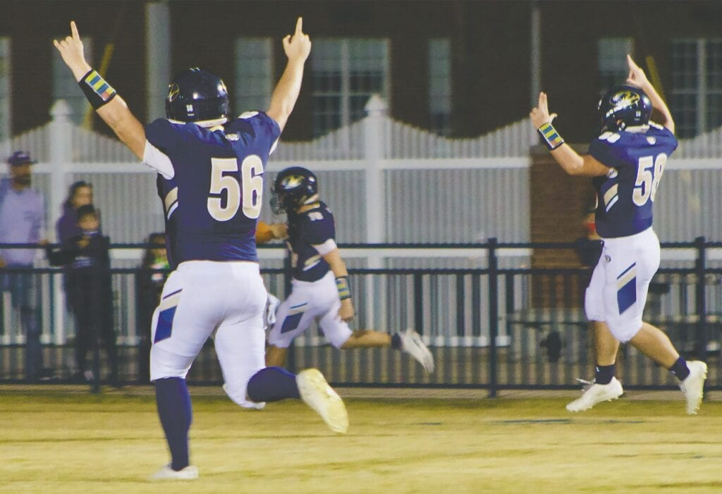 Sam Graves (56) and Zach Schultze (58) celebrate as John Williams (16) scores one of his three touchdowns. -Jennifer Cassity