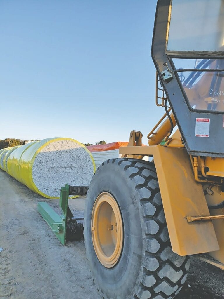 A large tractor is used to transport round bales into the gin.