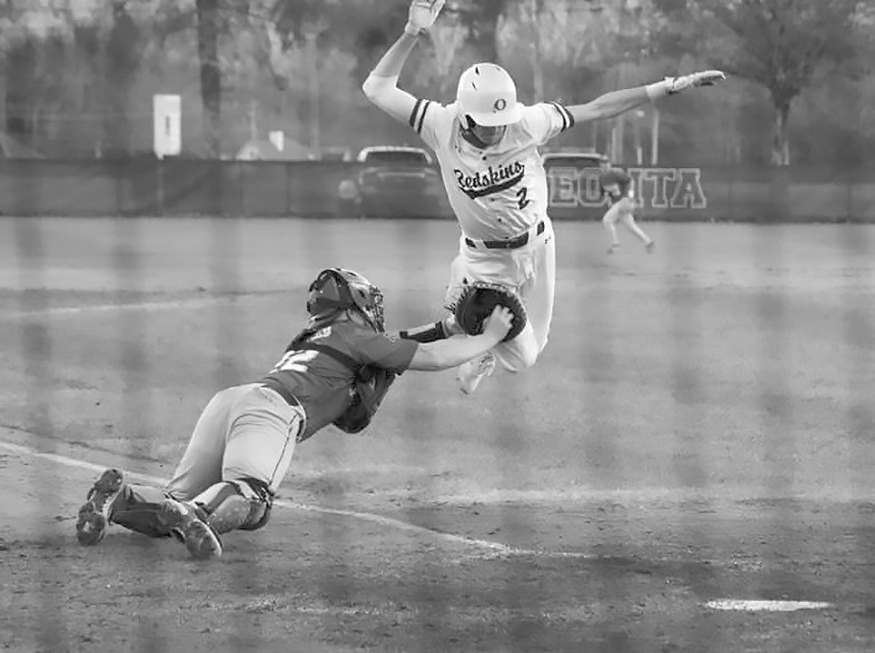 Oneonta's Andrew McElvey (2) leaps but cannot avoid being tagged at home. -Sandy McElvey