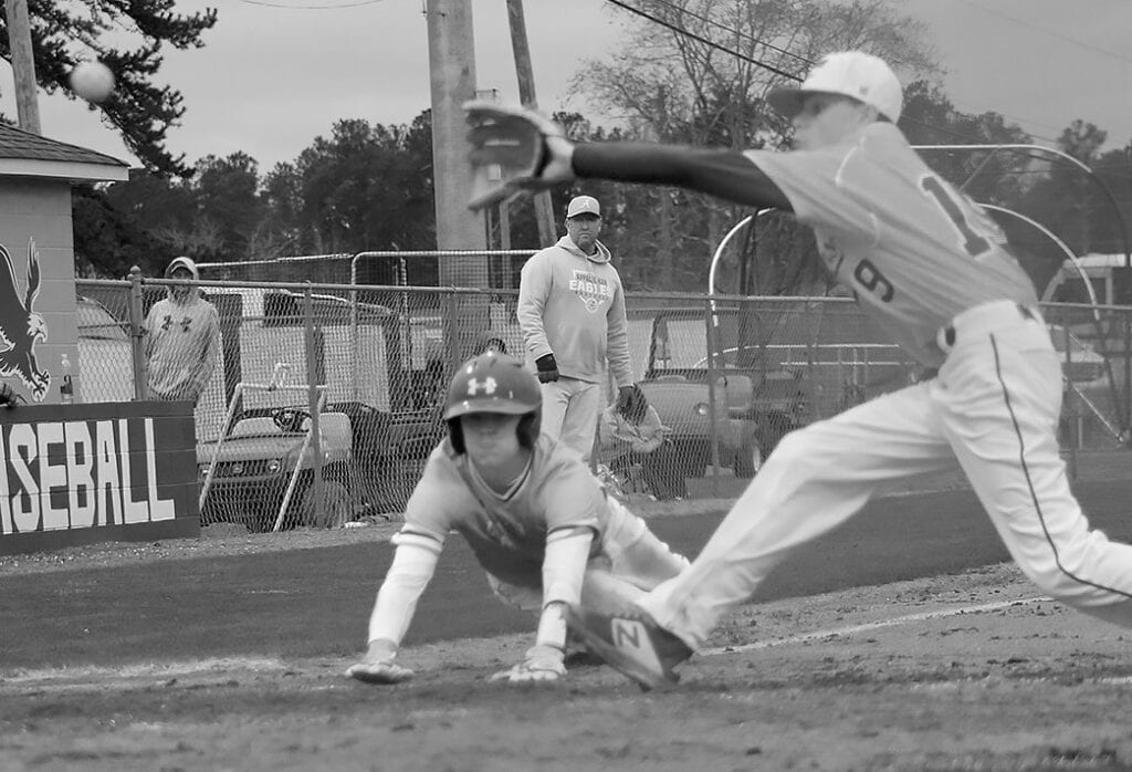 Appalachian's Logan Baswell (12) slides and beats the tag across home plate against Coosa Christian. -Kelli Clark