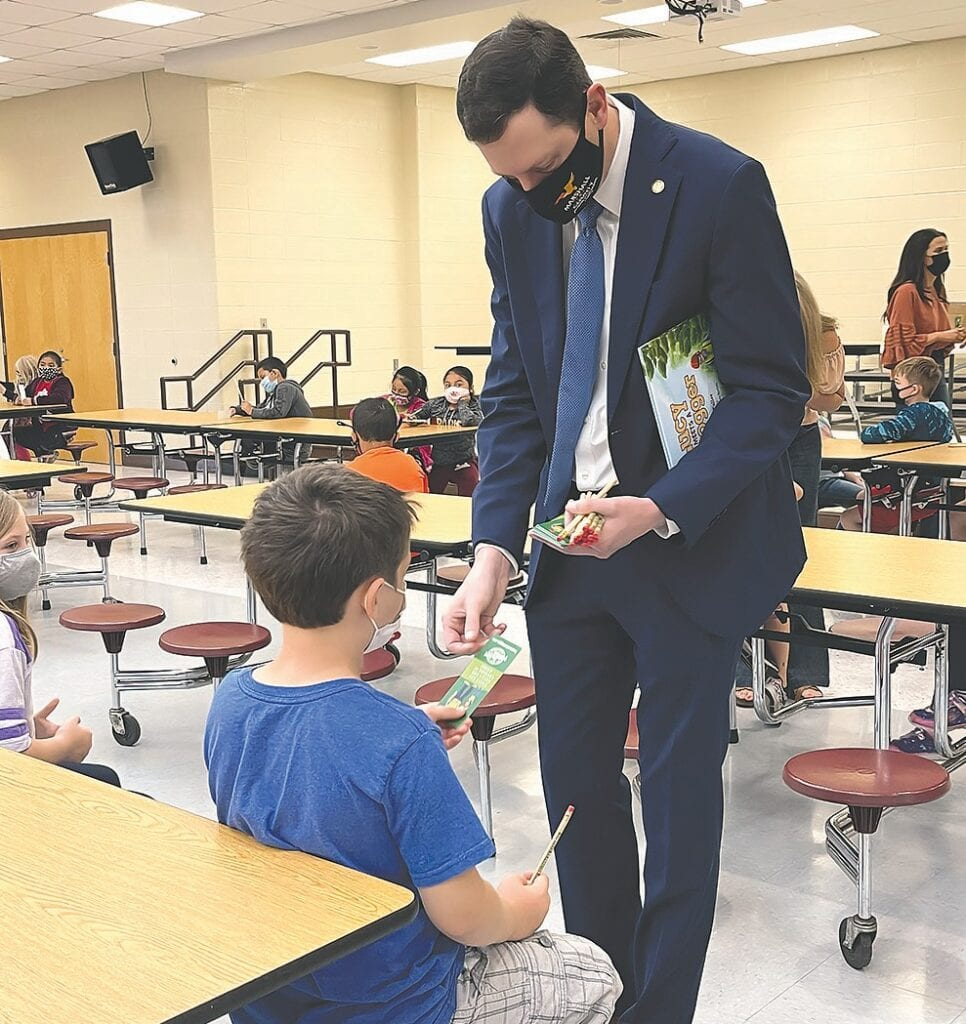 Sen. Clay Scofield distributes bookmarks and pencils to Blountsville Elementary students.