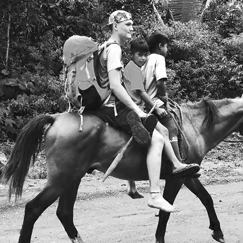 Drew Marbut catches a ride with Ecuadorian children. -courtesy Drew Marbut