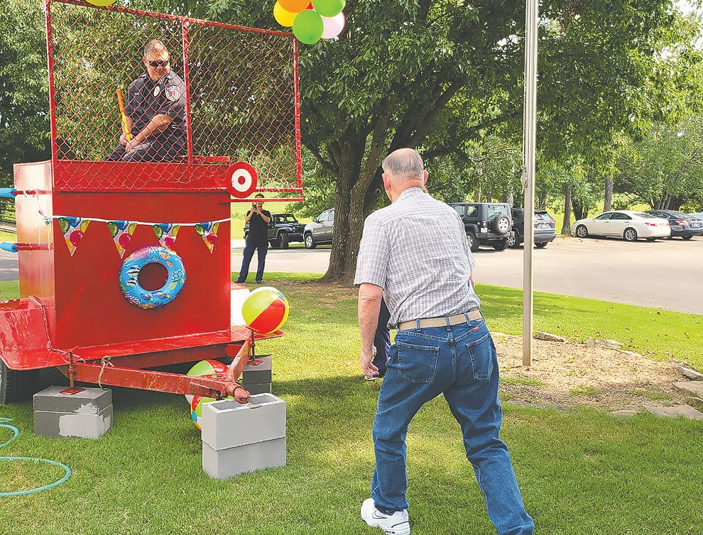 Oneonta Police Chief Charles Clifton eyes resident Tommy Pharris as he aims for the target. -TLC Nursing Center