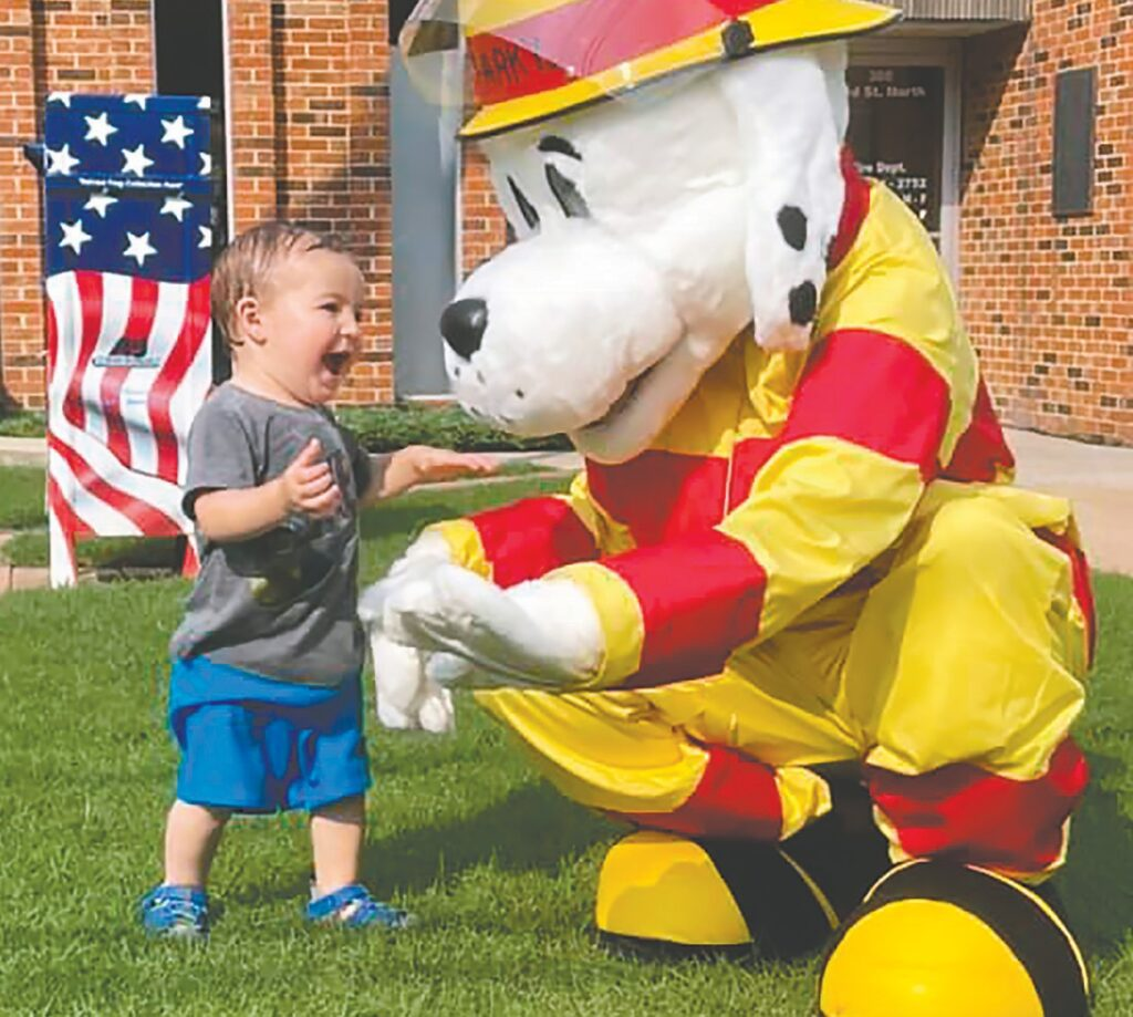 Hamilton Cole meets Sparky during Oneonta Fire Department's pop up splash pad Saturday. Hamy is the son of Ryan and Amanda (Oneonta City Clerk) Cole. -Amanda Cole