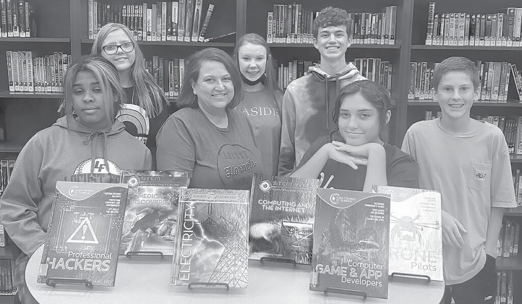 Locust Fork librarian Grindl Weldon (center) and students show off just a few of the books purchased with money from BCEF grants. -Grindl Weldon
